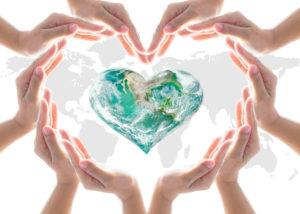 Hands around the heart shaped world